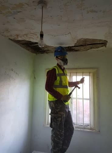 Anthony Birch pulling down the ceiling in the office