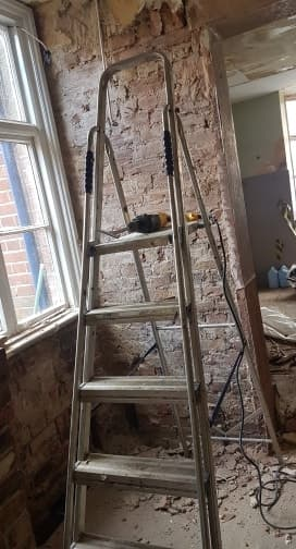 Ladder against a wall to allow removal of plaster on a lintel