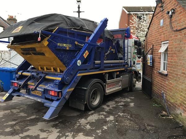Skip lorry squeezing out of the gates