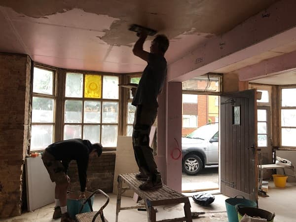 Ian plastering the ceiling on front left