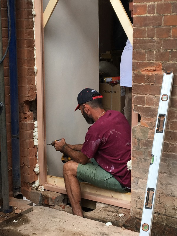 One of the professionals making the new door frame
