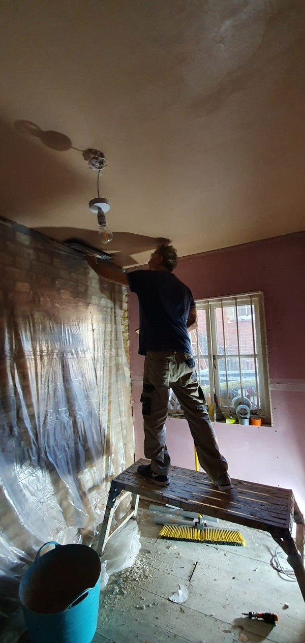 Standing on a platform to give him height required to plaster ceiling
