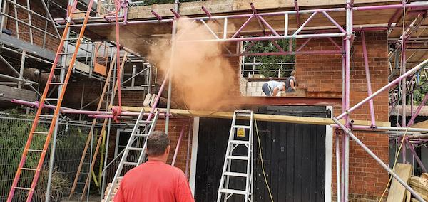 Plume of dust from bricks being cut on first floor